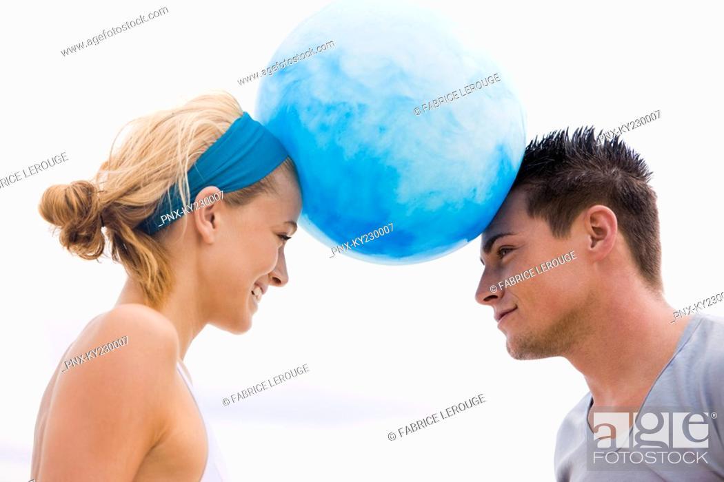 Stock Photo: Couple balancing beach ball between their heads.