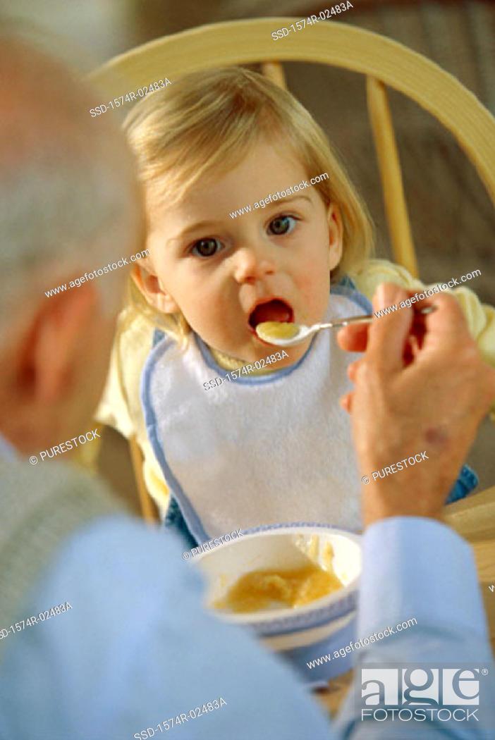 Stock Photo: Grandfather feeding his granddaughter.