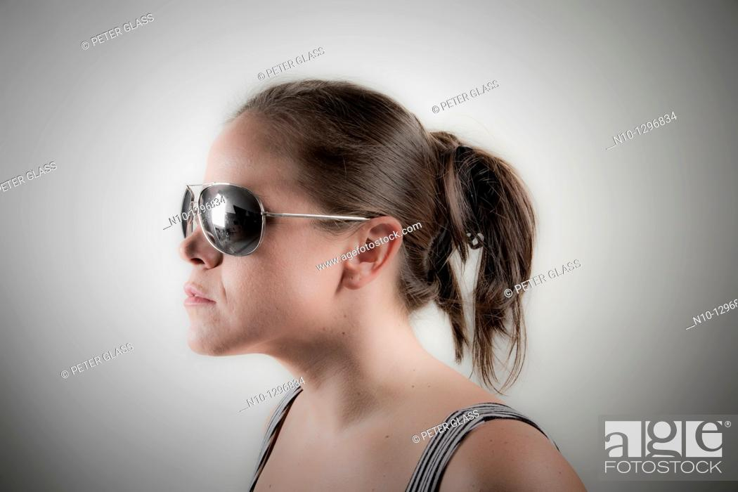 Stock Photo: Young woman wearing sunglasses.