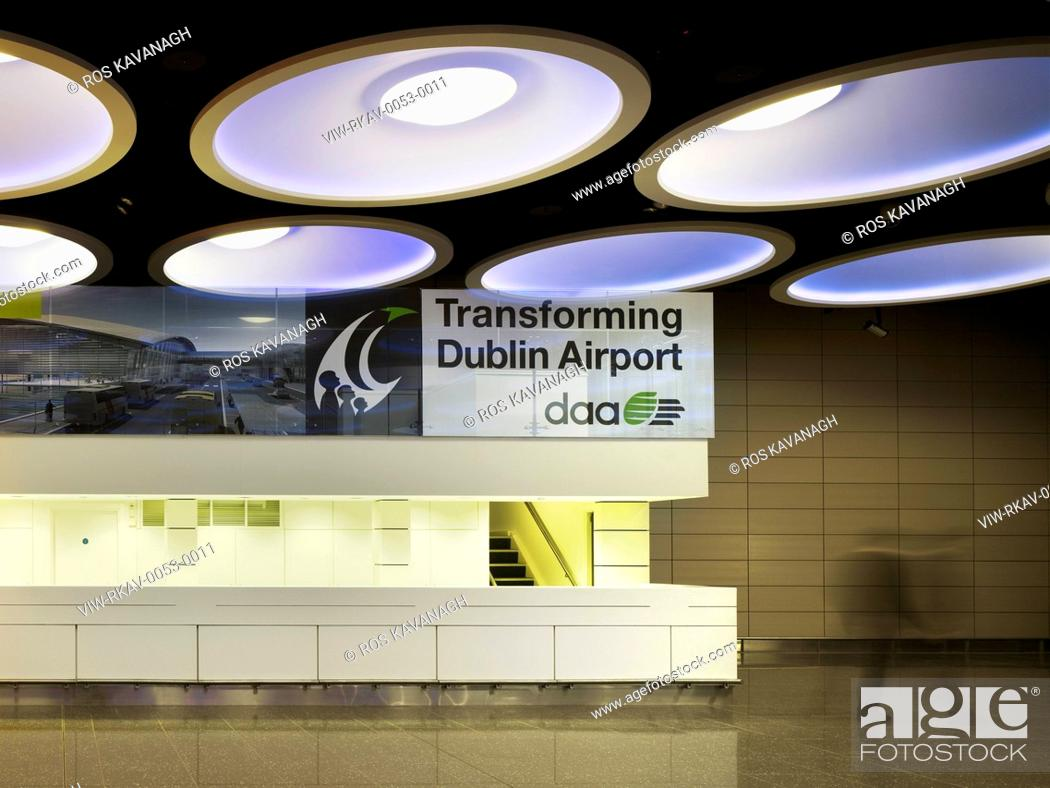 Stock Photo: Check In Facility, Dublin Airport, Dublin, Ireland. Architect: Moloney O'Beirne Architects, 2012. View of artificial lighting above information desk showing.