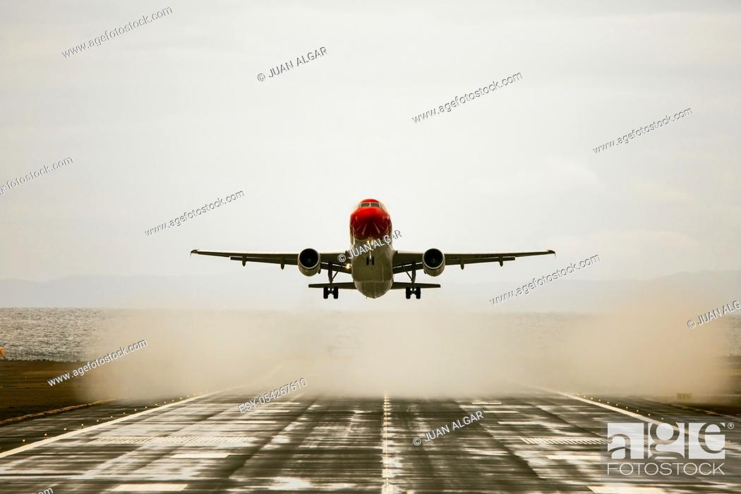 Stock Photo: Plane with red cockpit is about to land. Horizontal outdoors shot.