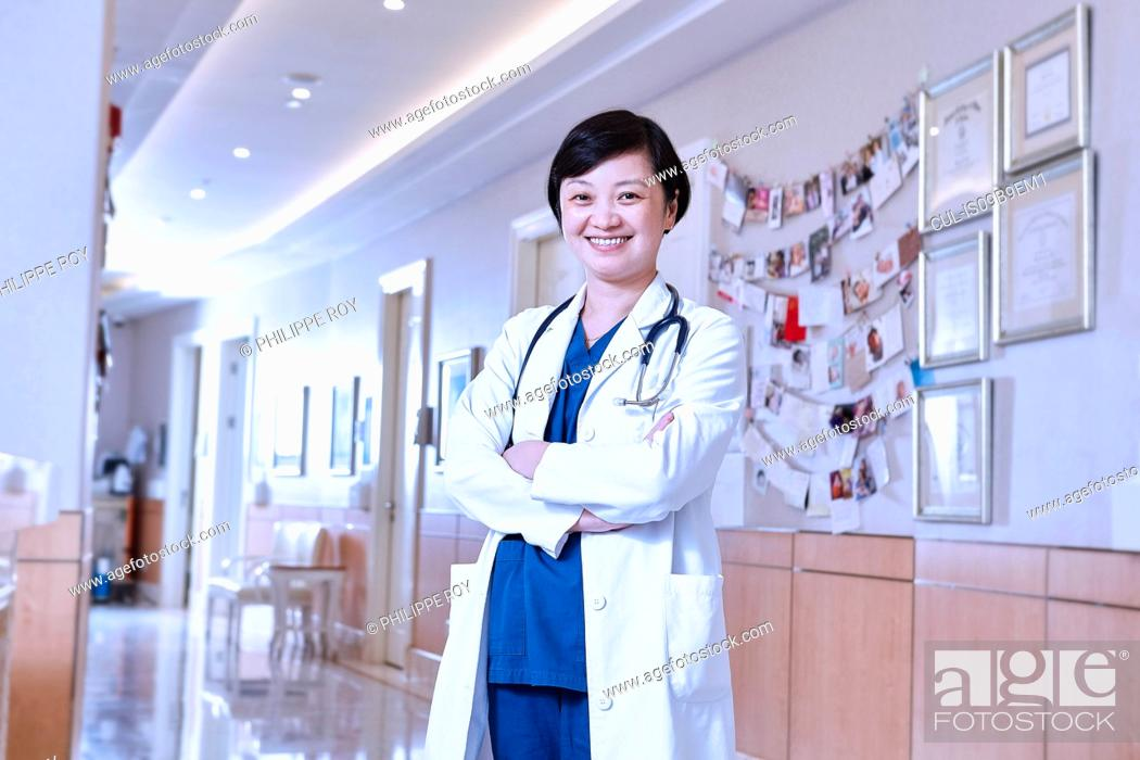 Stock Photo: Portrait of doctor in hospital corridor looking at camera smiling.