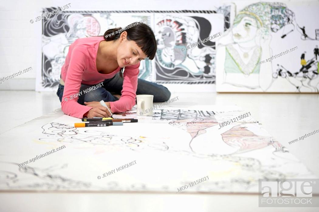 Stock Photo: Businesswoman drawing on large paper on floor.