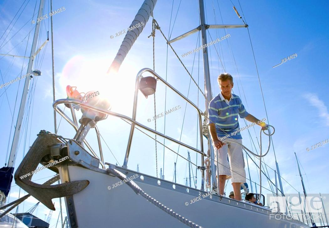 Stock Photo: Man standing on deck of moored sailing boat, holding rope lens flare.
