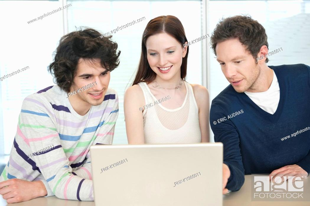 Stock Photo: Business executives using a laptop in an office.