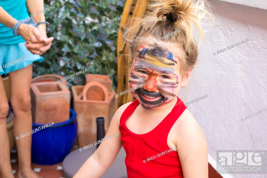 Stock Photo: portrait of three years old child with painted face, looking smiling and happy, next to woman with toy plastic handcuffs in terrace of house.