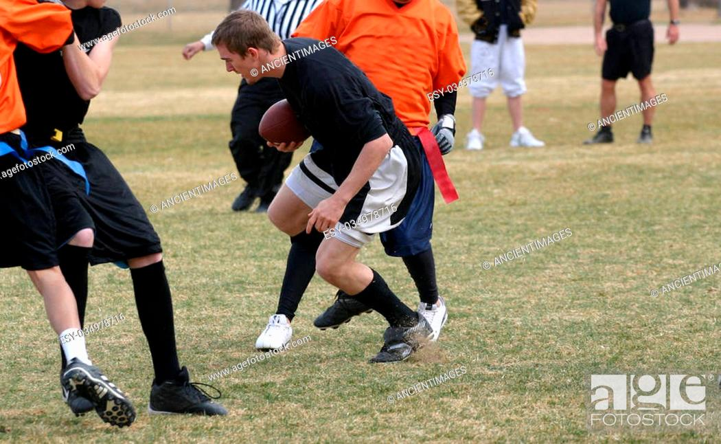 Imagen: A group of young men playing flag football in a park.