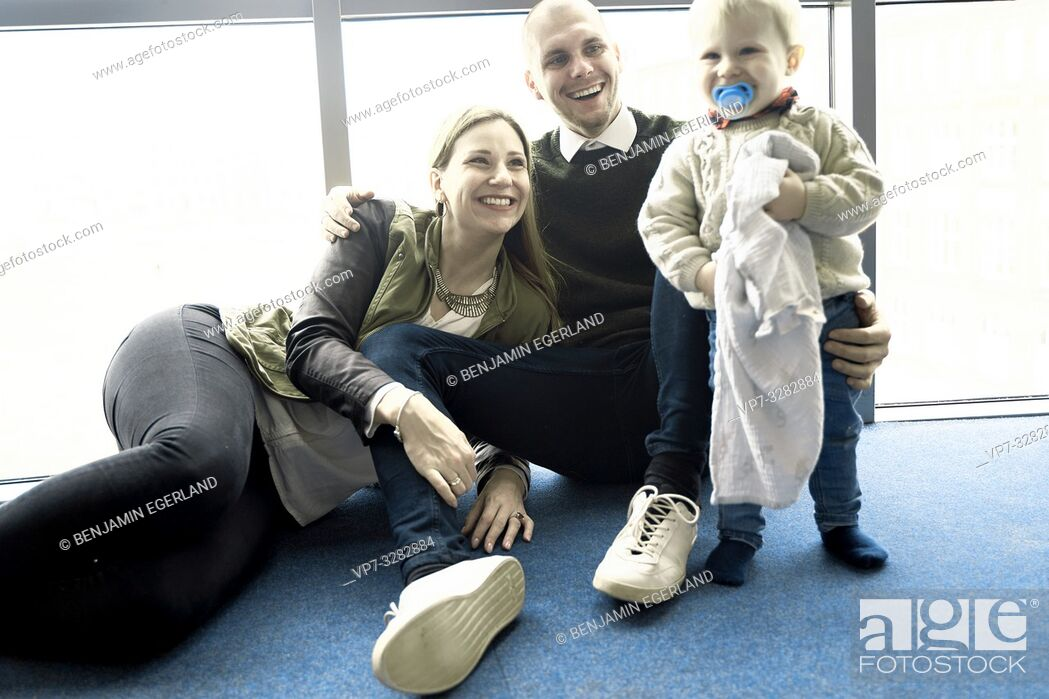 Stock Photo: little family, parents with baby toddler child sitting on blue floor at home, in Cottbus, Brandenburg, Germany.