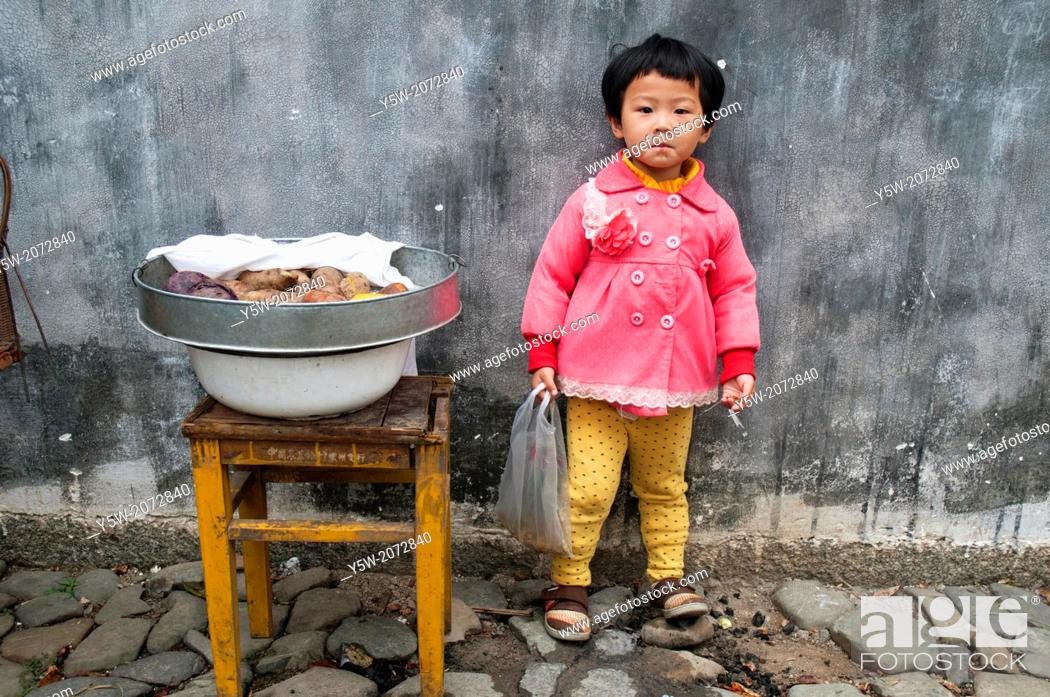 Stock Photo: Small girl minding a tray of vegetables in Chengkan village, Huizhou, Anhui, China.