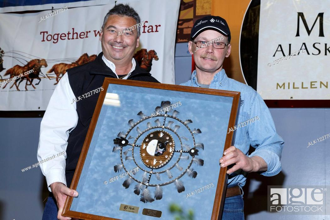 Imagen: Mitch Seavey (R) receives the PenAir Spirit of Alaska award from Danny Seybert of PenAir at the finishers banquet in Nome during Iditarod 2015.
