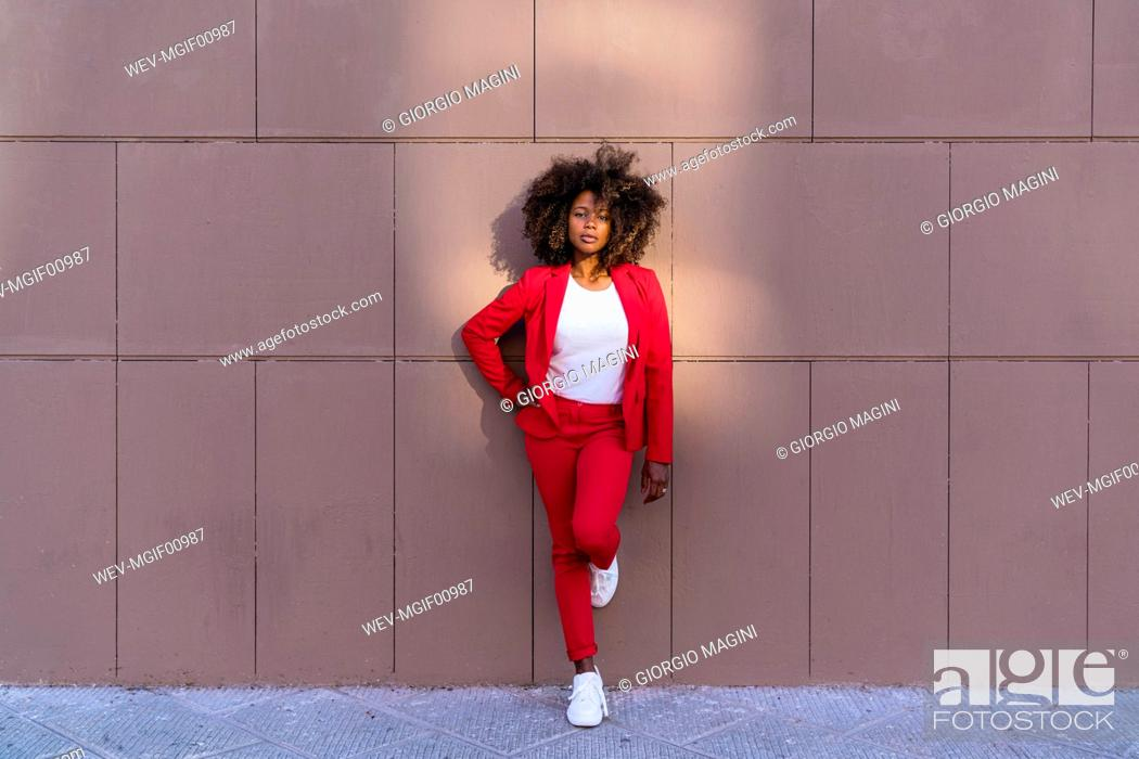 Stock Photo: Woman with hand on hip standing against brown wall.