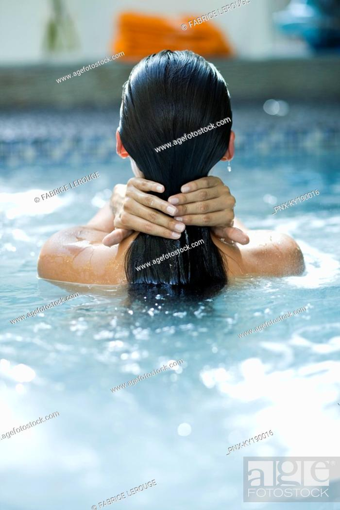 Stock Photo: Rear view of a woman in a swimming pool.