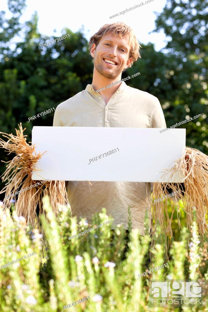 Stock Photo: Young man in scarecrow dressing and holding a blank placard in a field.