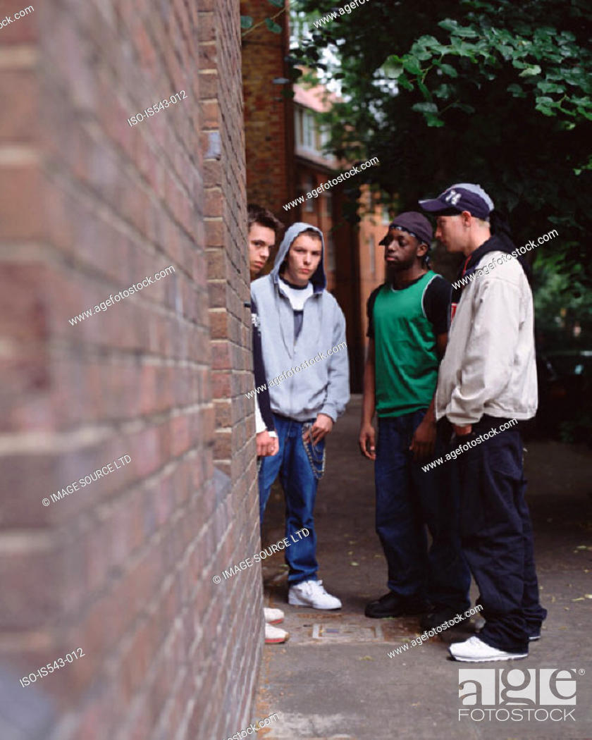 Stock Photo: Teenage boys standing by wall.