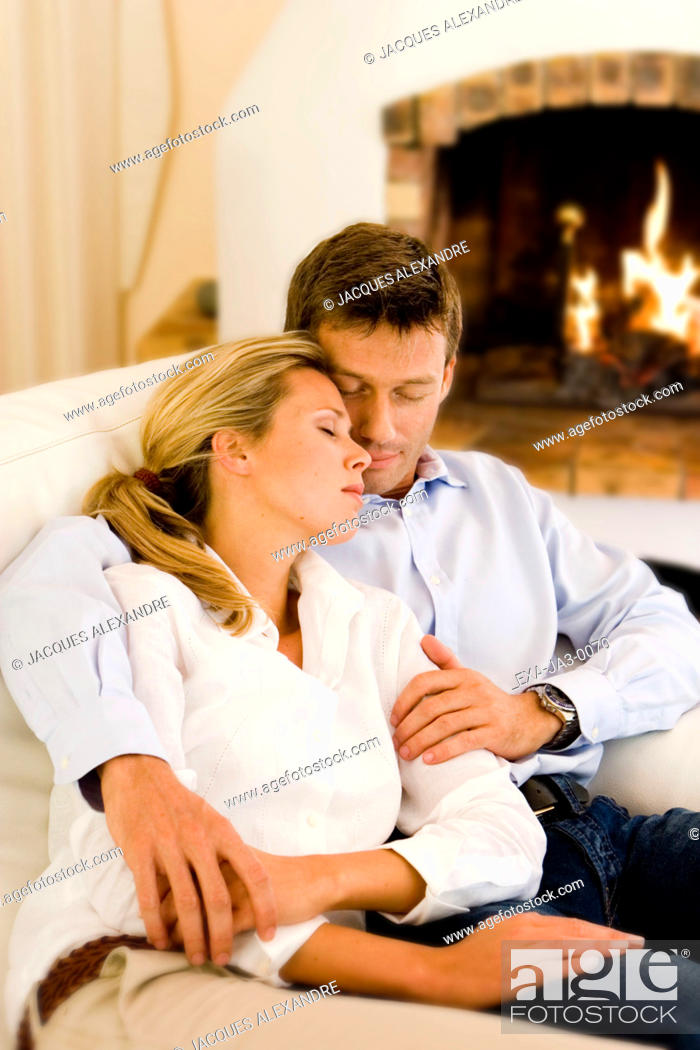 Stock Photo: Couple hugging on sofa with eyes closed.