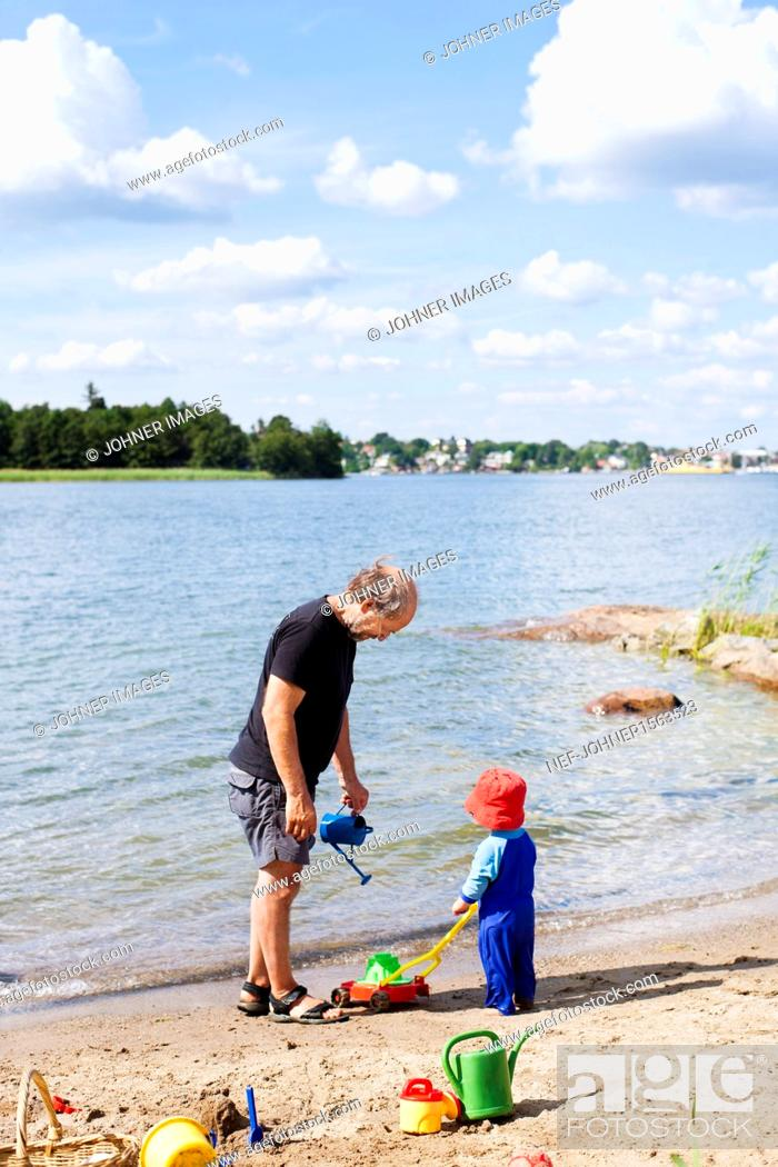 Imagen: Grandfather playing on beach with grandson.
