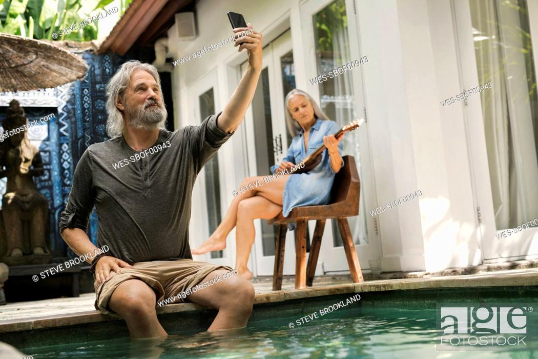 Imagen: Senior man taking selfie at poolside while his wife is playing the guitar.