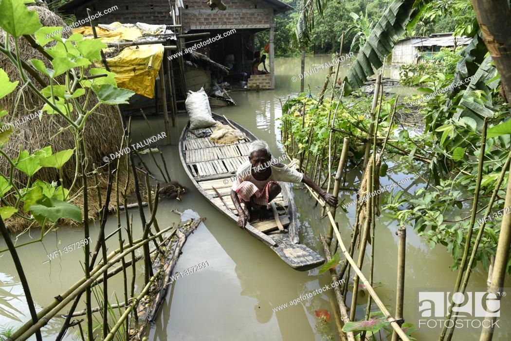 Stock Photo: A resident uses a country boat to move across a flooded area in Morigaon district of Assam, Monday, July 13, 2020.