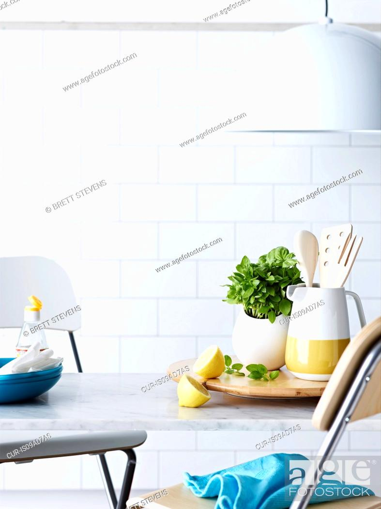 Stock Photo: Kitchen table with utensils, sliced lemon and herbs.