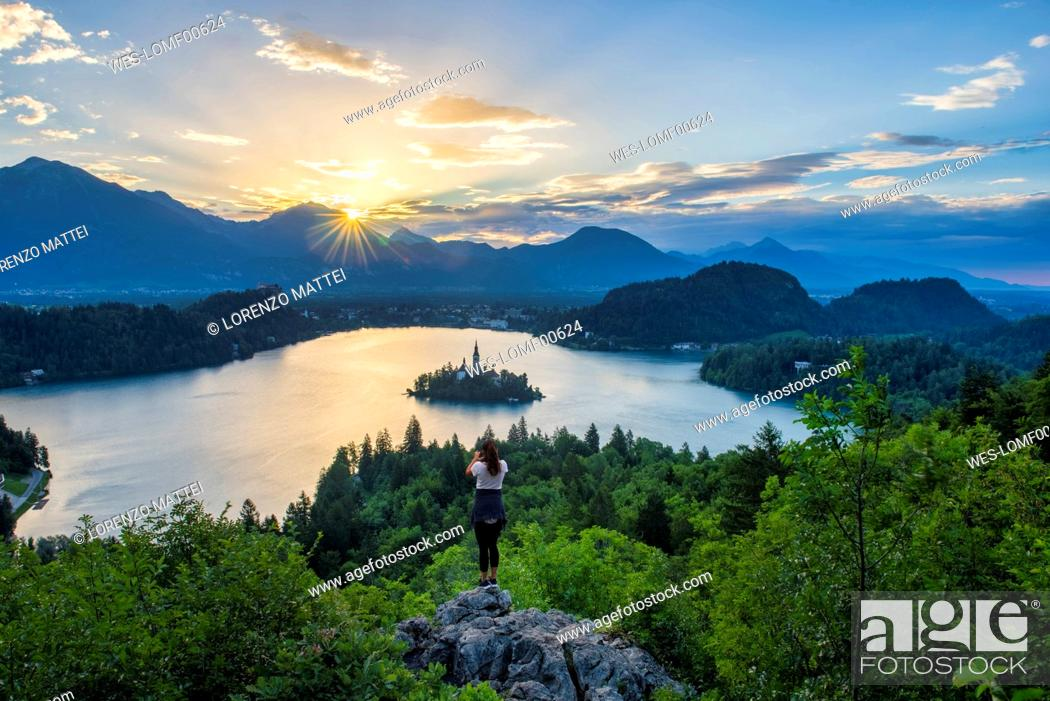 Stock Photo: Slovenia, Bled, Young woman taking picture of Bled island and Church of the Assumption of Maria at sunrise.