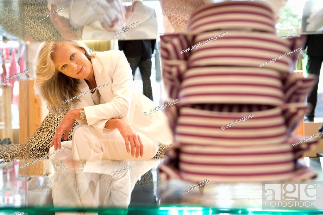 Stock Photo: Mature woman looking at shirts on shop counter.