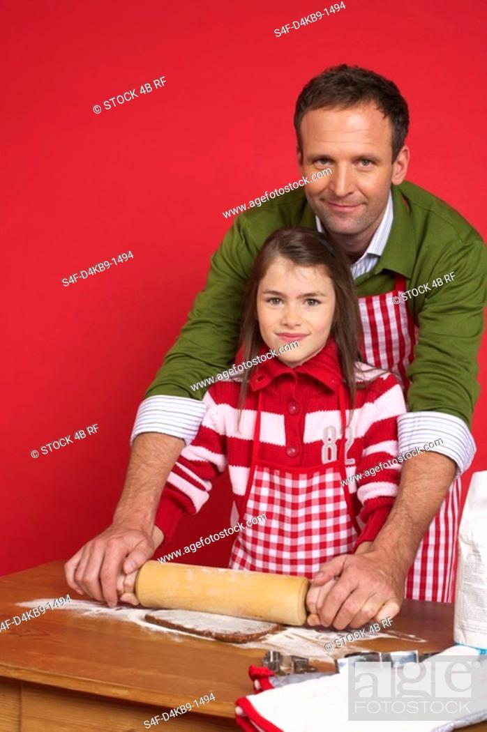 Stock Photo: Father and daughter baking Christmas cookies.