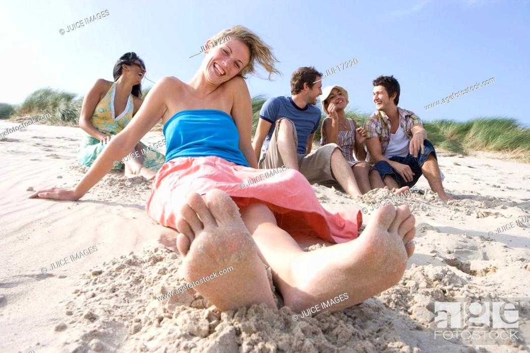 Stock Photo: Portrait of young woman sitting at beach, friends in background.
