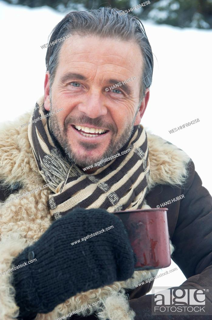 Stock Photo: Austria, Salzburg County, Mature man with tea cup in snow, smiling, portrait.
