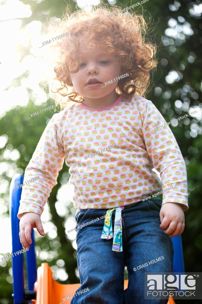 Stock Photo: A two year old girl on a slide in a garden.