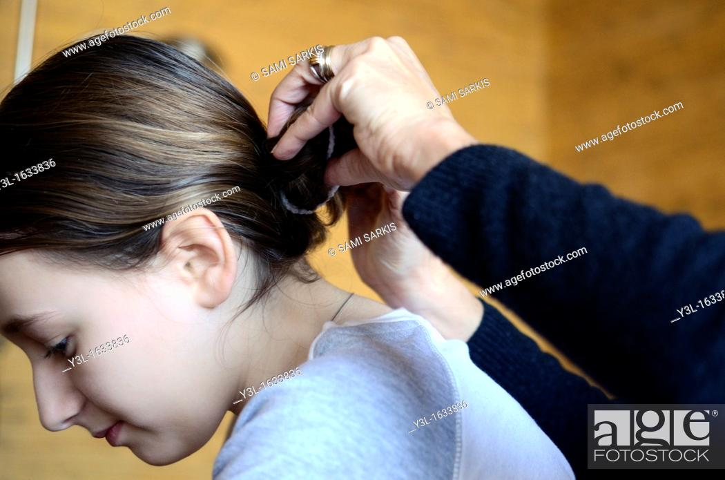 Stock Photo: Mother's hands fixing girl's hair.