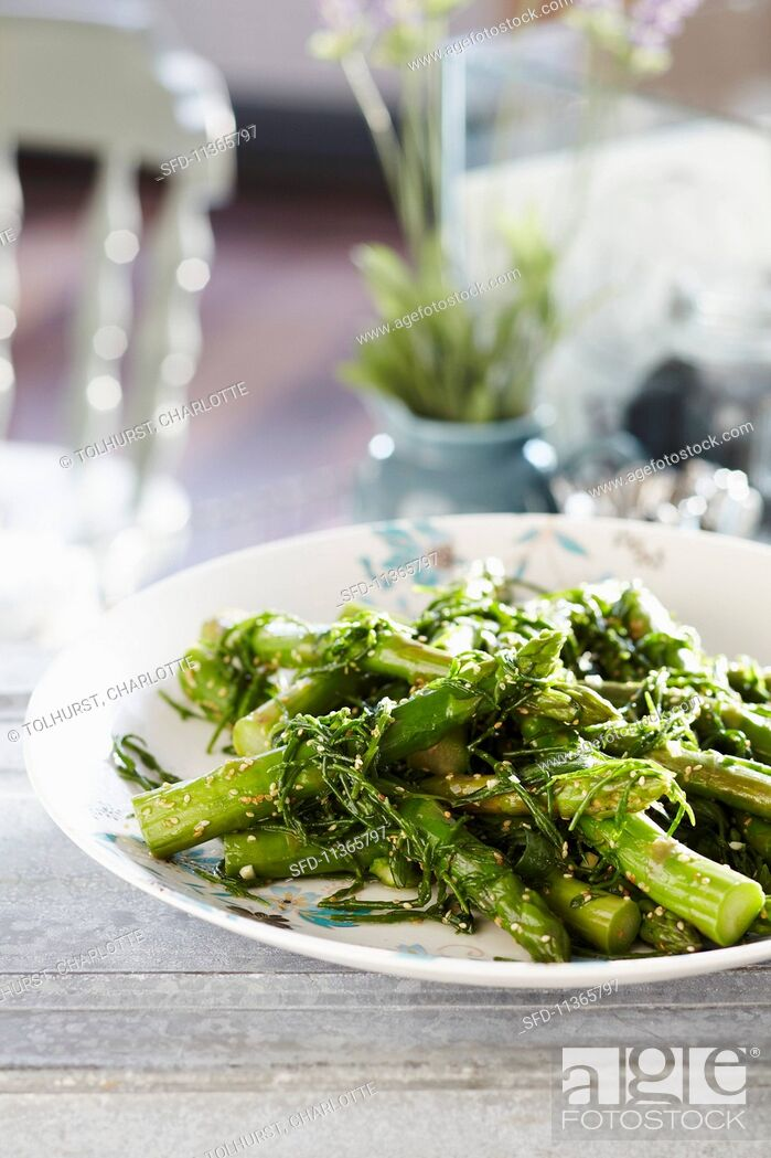 Stock Photo: Cooked asparagus with steamed rocket and sesame seeds.
