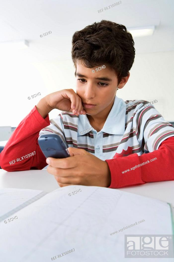 Stock Photo: School boy 10-13 using mobile phone in classroom, sitting looking at phone.