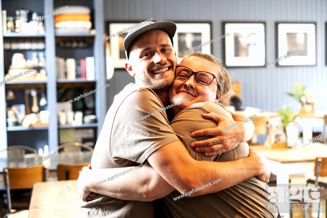 Stock Photo: Man wearing baseball cap and woman wearing glasses hugging, smiling at camera.