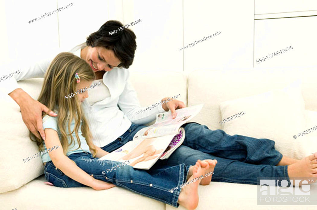 Stock Photo: Young woman reading a magazine with her daughter on a couch.