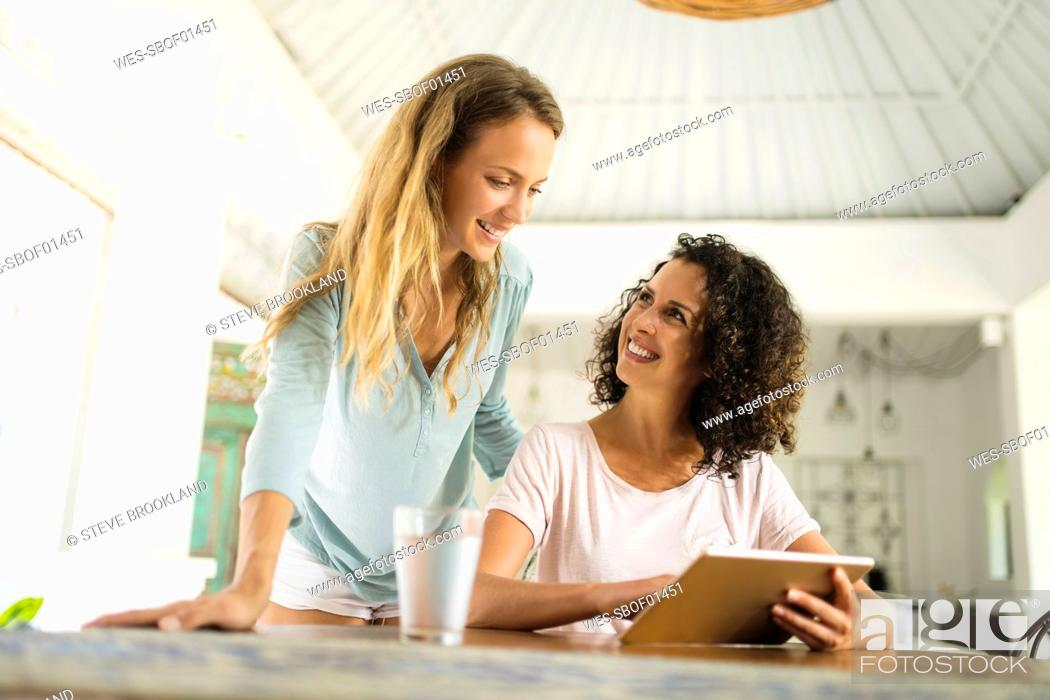 Stock Photo: Two smiling women at home using tablet.