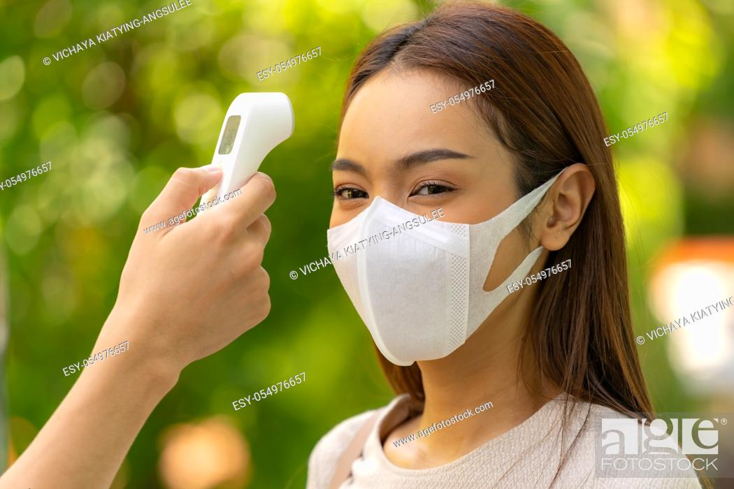 Stock Photo: Take Temperature asian woman with face mask before getting in building for new normal lifestyle after coronavirus covid-19 pandemic.