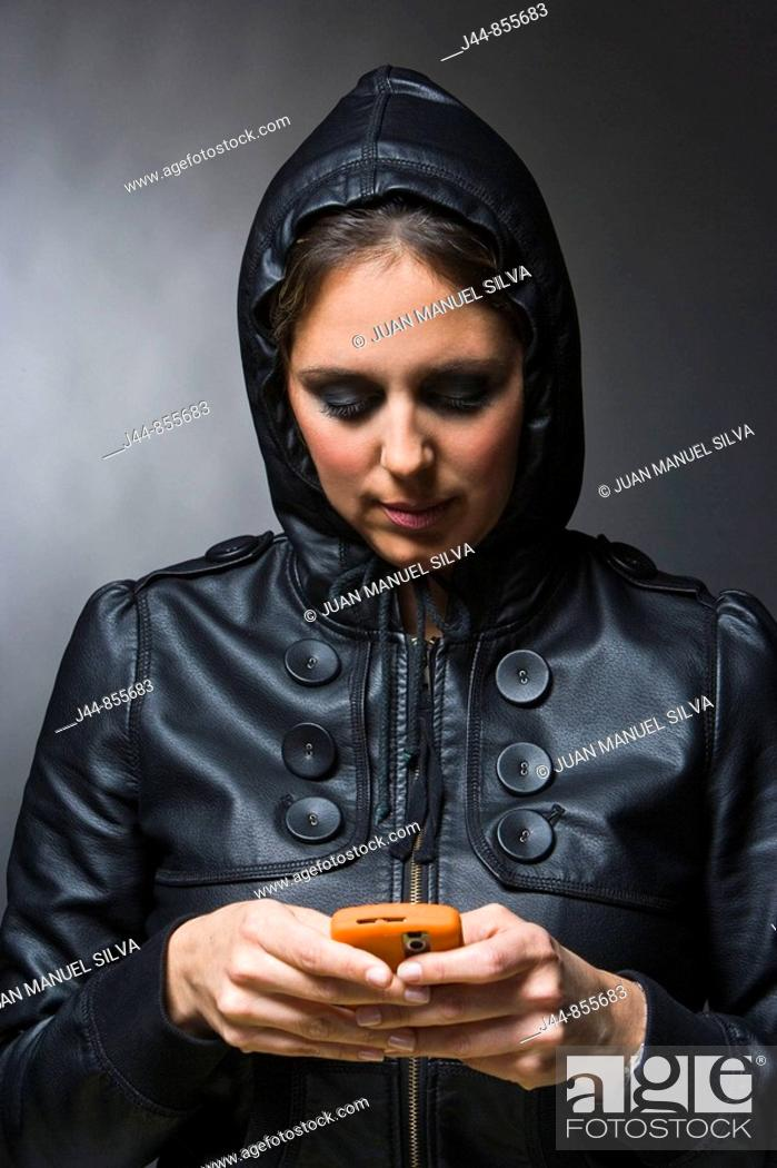 Stock Photo: Woman with leather jacket and hood using mobile phone.