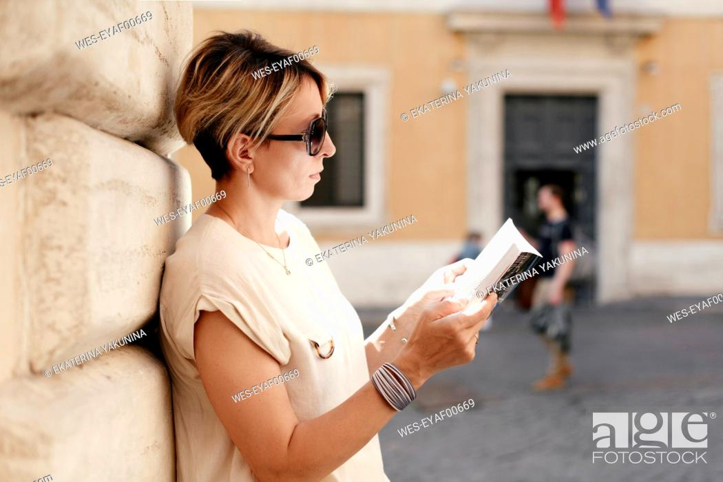 Stock Photo: Woman looking into a guidebook in the city, Rome, Italy.