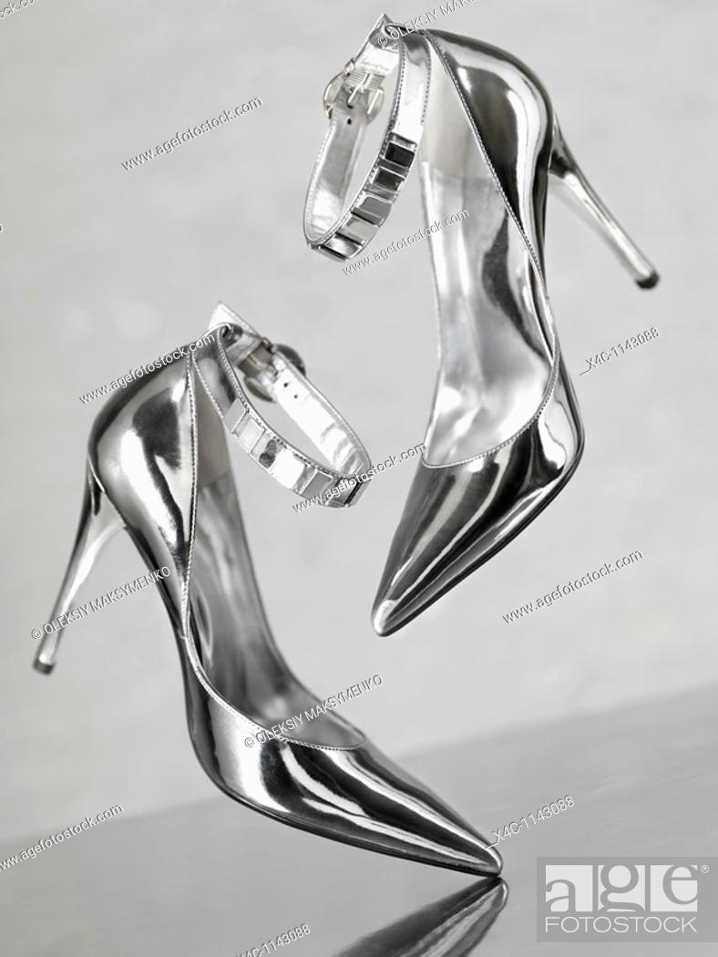 Stock Photo: Stylish shiny silver stiletto high heel shoes falling on metal surface.