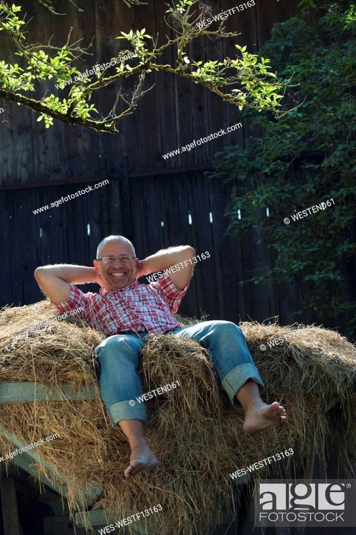 Stock Photo: Germany, Bavaria, Senior man lying on haystack.