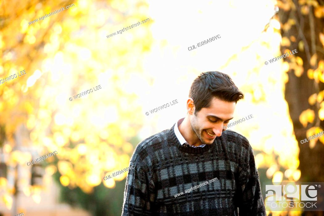 Stock Photo: Young man looking down in sunlit park, smiling.