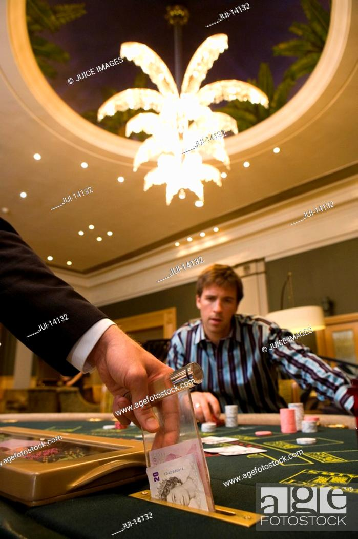 Stock Photo: Croupier putting money in slot of gambling table, section.