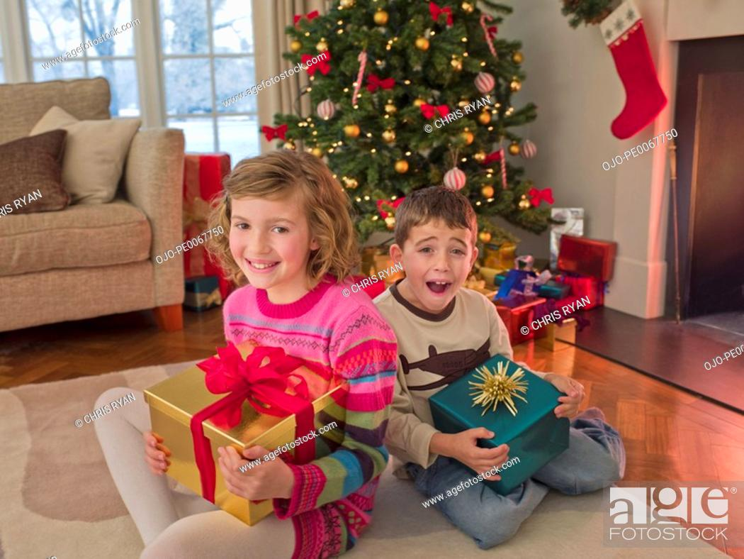 Stock Photo: Boy and girl holding Christmas gifts in living room.