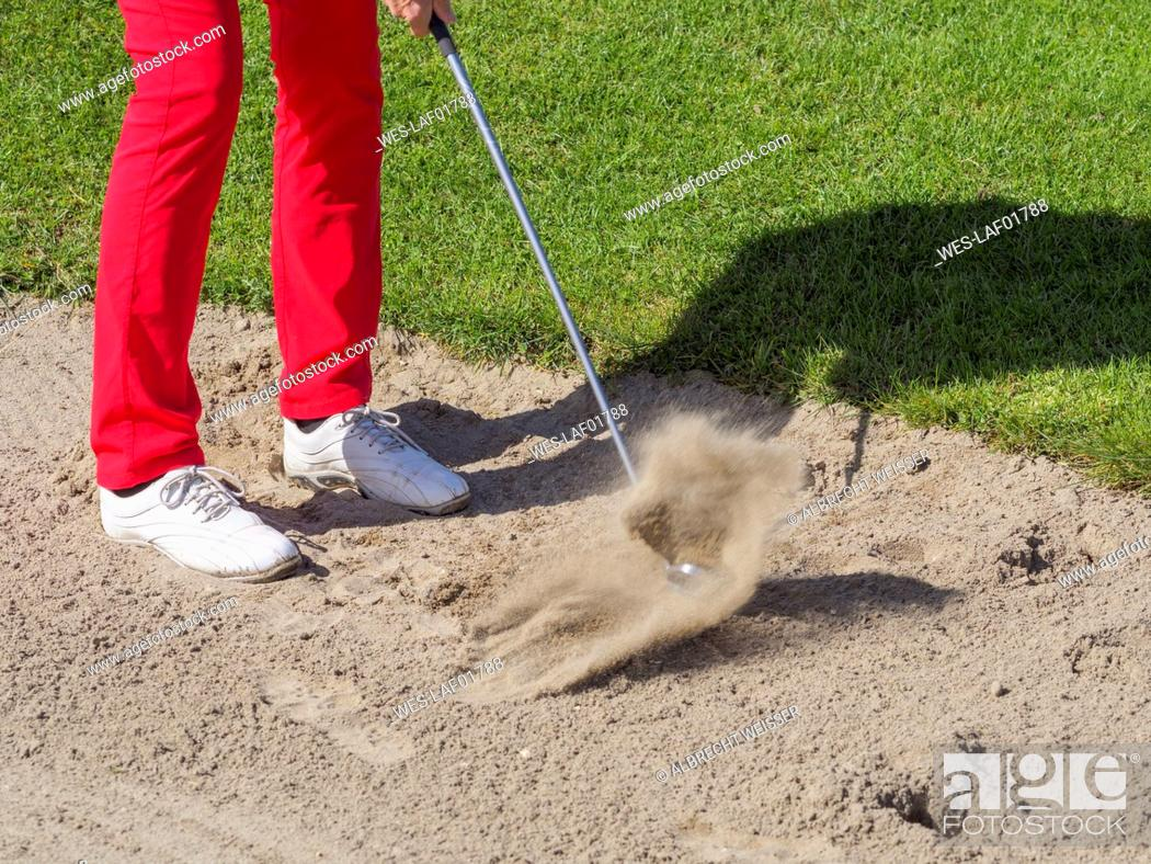 Stock Photo: Golfer playing bunker shot, partial view.