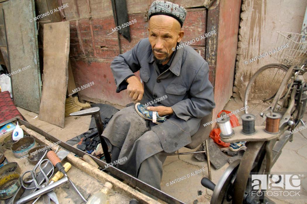 Stock Photo: A uigur cobbler repair a shoe in Kashgar downtown. Kashgar city. Xinjiang province. China. Asia.