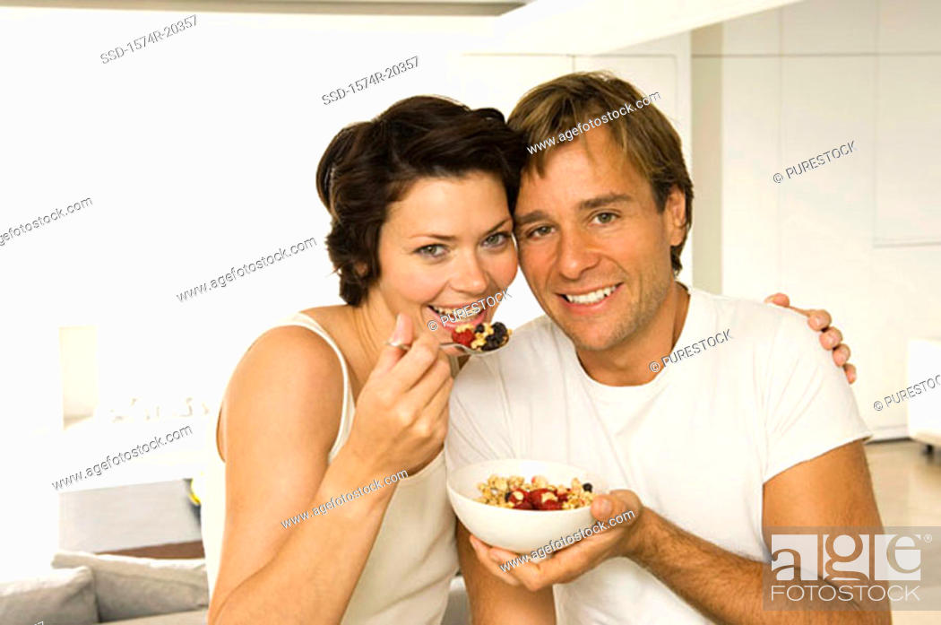 Stock Photo: Portrait of a young couple eating fruit salad and smiling.