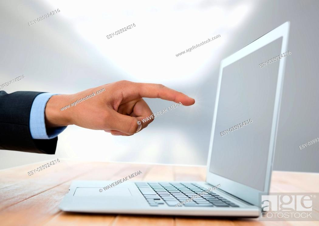 Stock Photo: Business hand with laptop at desk with bright background.