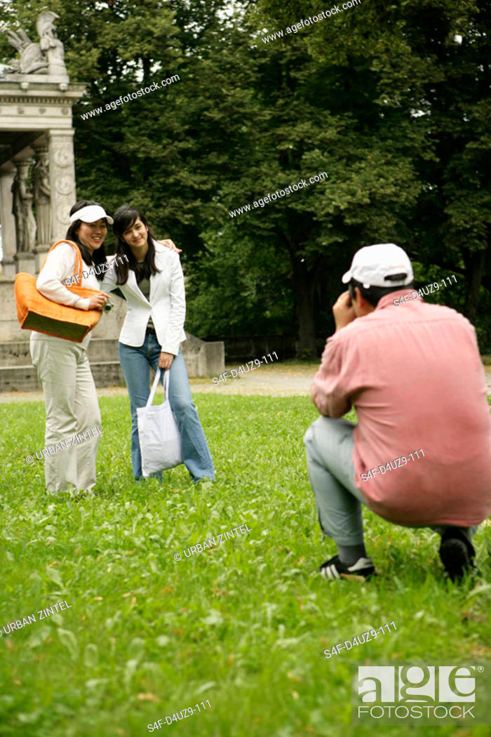 Stock Photo: Man taking a picture of two Asian women in a park.