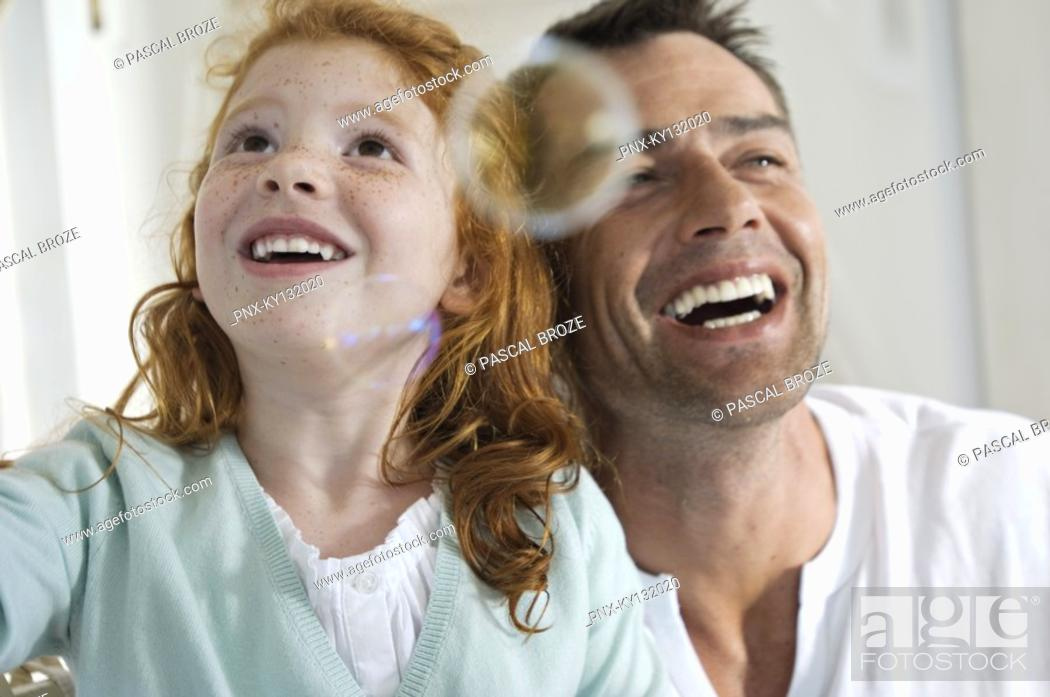 Stock Photo: Portrait of father and daughter laughing, looking at soap bubbles, indoors.