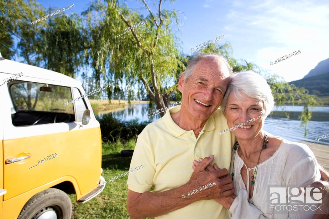 Stock Photo: Senior couple arm in arm by lake and camper van, smiling, portrait.